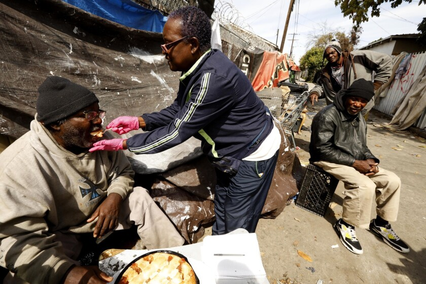 Rose Rios feeds pie to Donald Shields, 59, who is legally blind and living in an alley in South Los Angeles. Shields is being taken care of by childhood friends Wayne Robinson, 58, right, and Daniel Murray, 59, background.