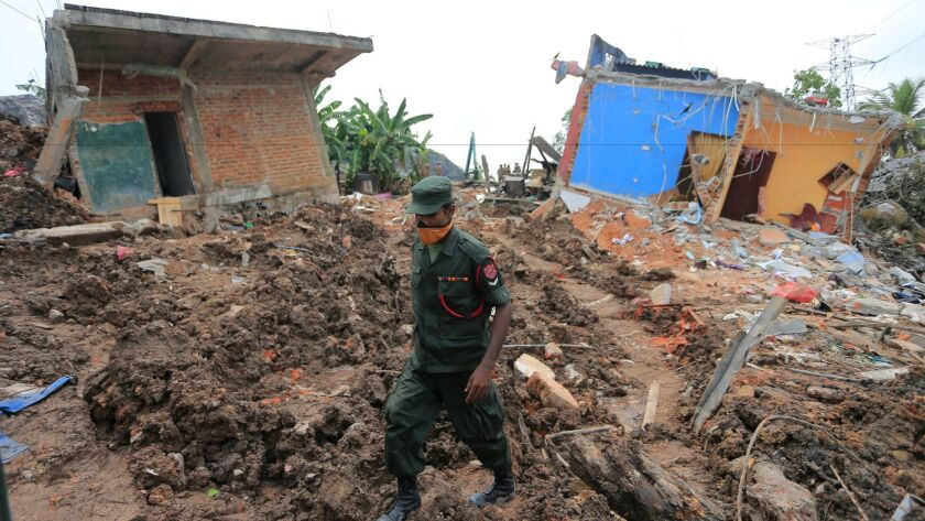 A Sri Lankan army soldier walks past damage houses after garbage collapse in Meetotamulla, on the ou