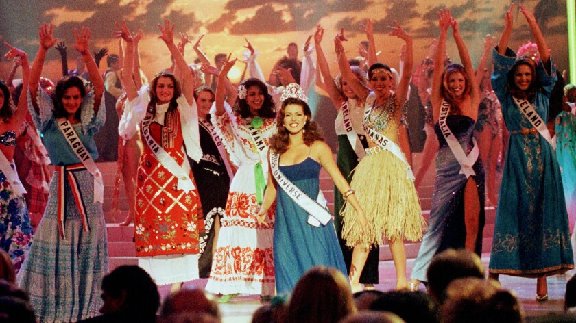 Miss Universe of 1996 Alicia Machado, center, of Venezuela dances with the 74 contestants of the Miss Universe pageant in Miami Beach.