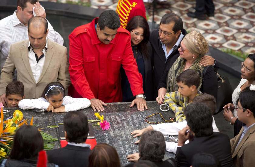 Venezuelan President Nicolas Maduro, center, gathers at the tomb of late President Hugo Chavez with Chavez's family and government officials to mark the second anniversary of Chavez's death.