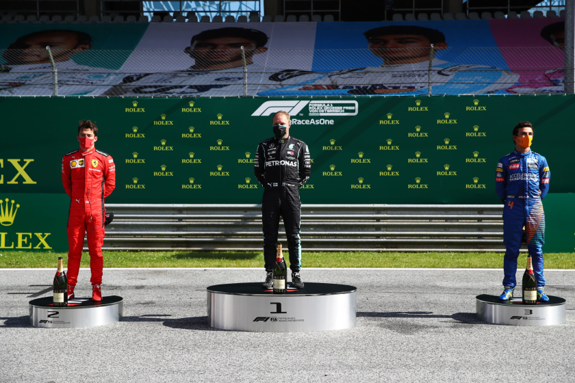 Valtteri Bottas, center, stands between second-place finisher Charles Leclerc, left, and third placed Lando Norris