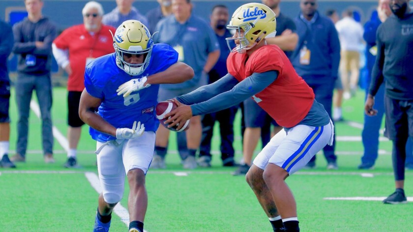UCLA quarterback Dorian Thompson-Robinson fakes a hand-off to running back Martell Irby during a spring practice session.