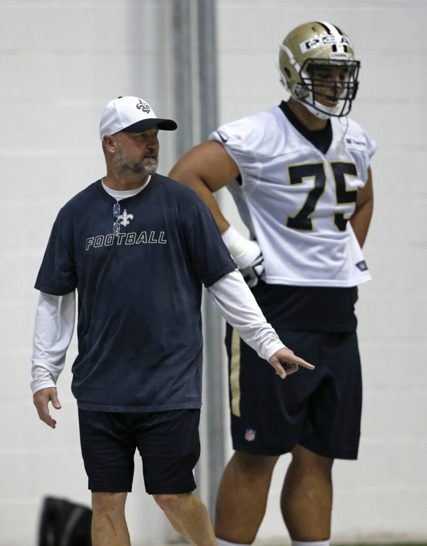 New Orleans Saints offensive line coach Dan Roushar gives instruction as offensive guard Andrus Peat (75) looks on during NFL football practice in Metairie, La., Thursday, June 2, 2016. (AP Photo/Gerald Herbert)
