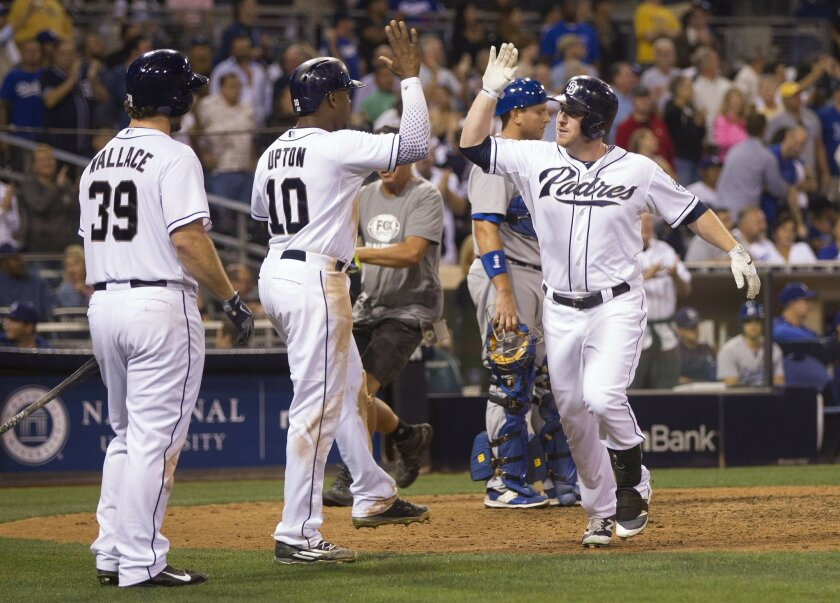 San Diego Padres vs. Los Angeles Dodgers. Jed Gyorko is congratulated by San Diego Padres left fielder Justin Upton (10) and San Diego Padres first baseman Brett Wallace (39) after hitting a two run HR in the 8th.
