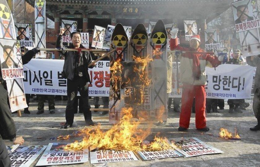 South Koreans in Seoul burn an image of North Korean leader Kim Jong Un and representations of a North Korean missile as they protest the North's rocket launch this week.
