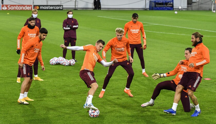 Real Madrid's Toni Kroos, center, and Real Madrid's Sergio Ramos, right, exercise during a training session prior the Champions League group B soccer match between Borussia Moenchengladbach and Real Madrid in Moenchengladbach, Germany, Monday, Oct. 26, 2020. (AP Photo/Martin Meissner)