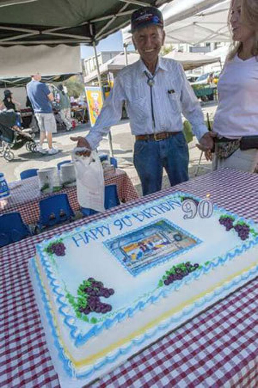 Harry Nicholas receives a cake for his 90th birthday celebration at the Beverly Hills market.