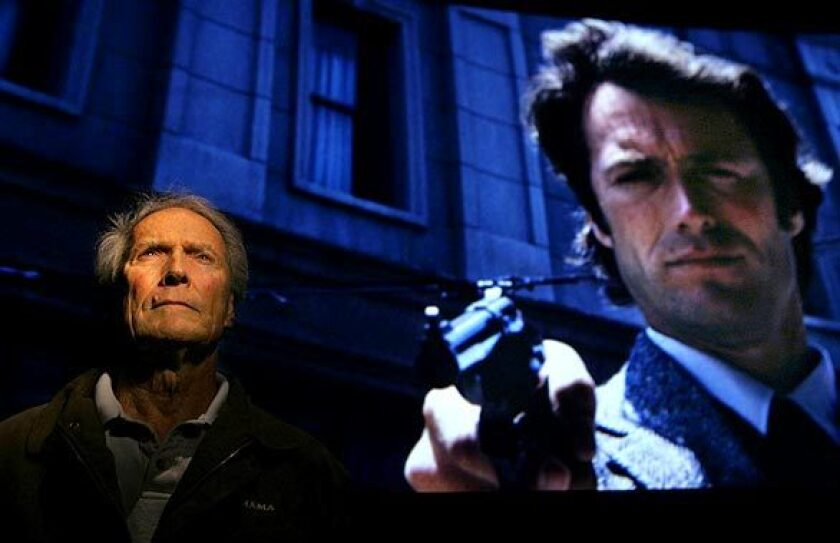 """Clint Eastwood stands before a screen projecting a scene from his 1971 film """"Dirty Harry"""" at the Steven J. Ross Theater on the Warner Bros. lot in Burbank. Warner Bros. is releasing a boxed set of the Dirty Harry films, in which Eastwood portrayed San Francisco police Inspector Harry Callahan. """"Who's that young fella?"""" cracked Eastwood, gazing up at the screen."""