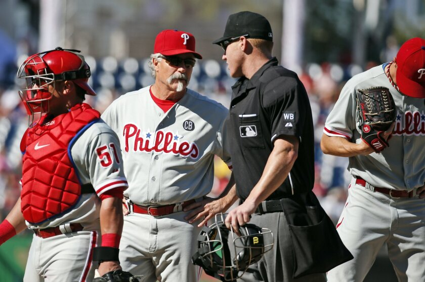 Philadelphia Phillies pitching coach Bob McClure, second from left, speaks with home plate umpire Tom Woodring, as Woodring breaks up a meeting on the mound with catcher Carlos Ruiz, left, and starting pitcher Cole Hamels, during the seventh inning of a baseball game at Nationals Park, Sunday, Sept. 7, 2014, in Washington. The Nationals won 3-2. (AP Photo/Alex Brandon)