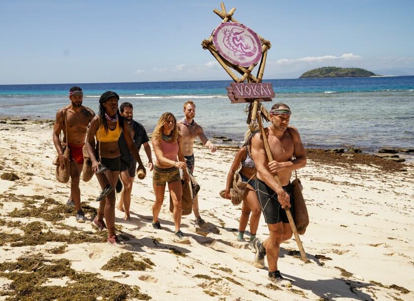 """Survivor: Island of Idols"" contestants walk across a sandy beach."