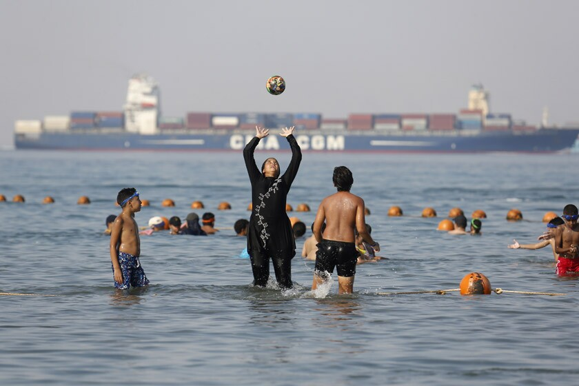 A woman in a burkini joins others at a beach in Suez, Egypt, in 2018.