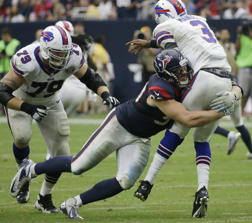 ADVANCE FOR WEEKEND EDITIONS, OCT. 4-5 - FILE - In this Sept. 28, 2014, file photo, Houston Texans' J.J. Watt (99) hits Buffalo Bills' EJ Manuel (3) during the second quarter of an NFL football game in Houston. The Texans (3-1) play the Dallas Cowboys (3-1) on Sunday, Oct. 5. ((AP Photo/David J. Phillip, File)