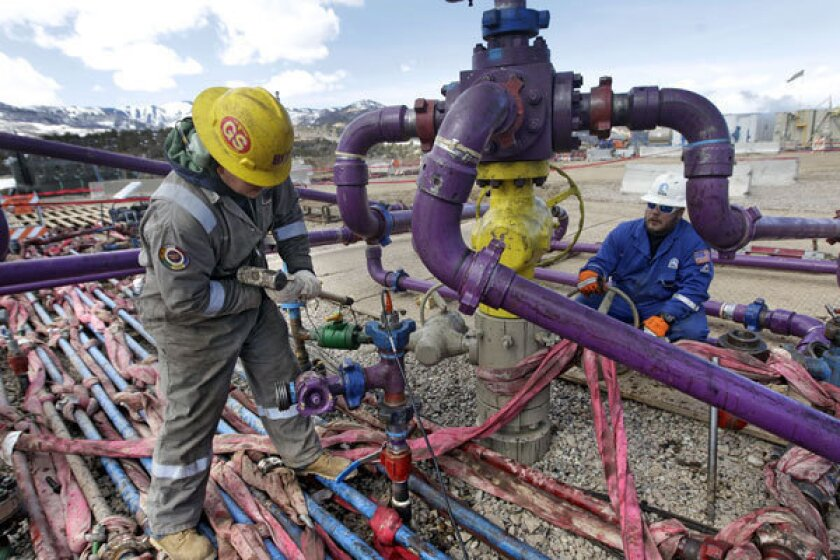 Workers tend to a well head at a hydraulic fracturing operation in Rifle, Colo.
