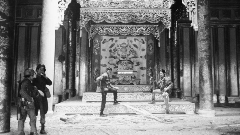 Vietnamese soldiers pose in victory in the ornate throne room of the Imperial Palace in the Citadel