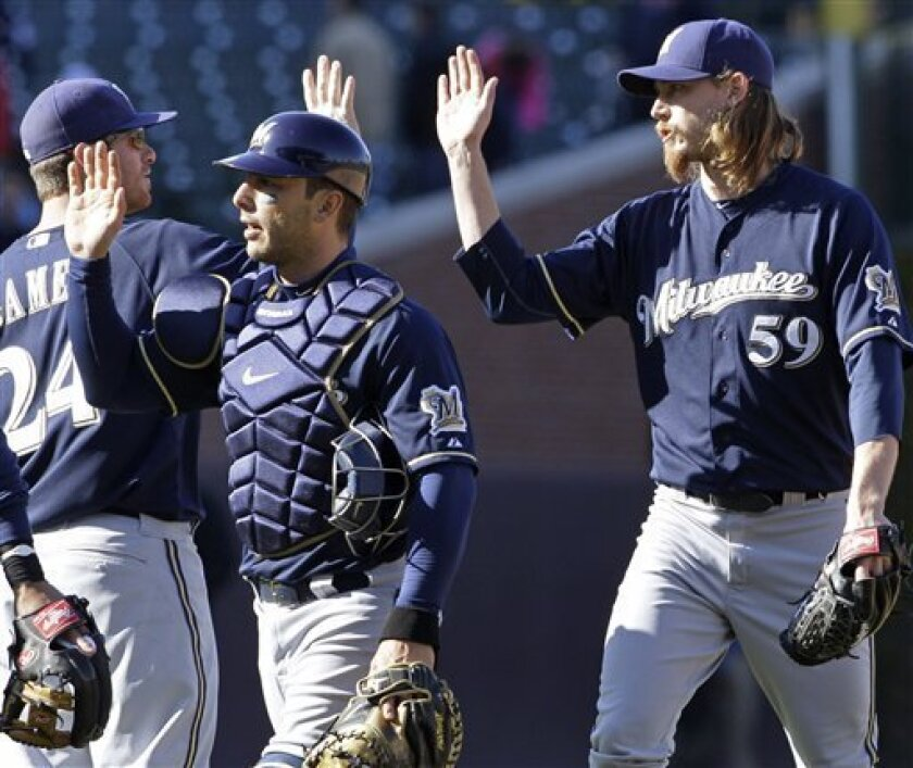 Milwaukee Brewers closer John Axford, right, catcher George Kottaras, center, and Mat Gamel celebrate after the Brewers defeated the Chicago Cubs 2-1 in a baseball game in Chicago, Wednesday, April 11, 2012. (AP Photo/Nam Y. Huh)