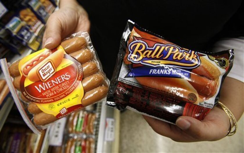 A store employee holds packages of hot dogs at a local Dahl's grocery store, Friday, May 22, 2009, in Des Moines, Iowa. Hot dog sales are growing as people look for ways to eat on the cheap. But the scramble to claim this $2.1 billion market has landed the makers of the nation's best selling hot do