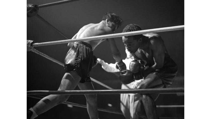 March 11, 1947: Manuel Ortiz, left, throws a blow that glances off the face of Harold Dade late in their bantamweight title bout.