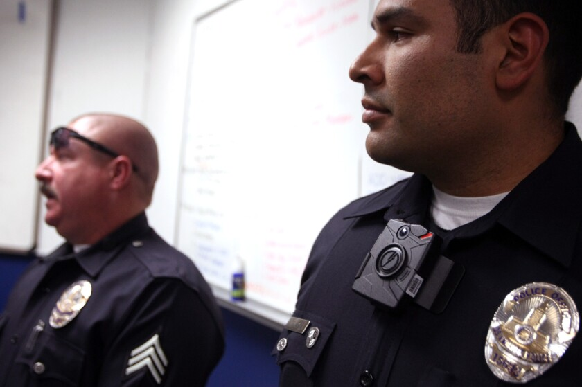 Los Angeles Police Officer Mendoza, right, wears a Taser Axon clip-on camera on his collar at a January news conference regarding the new on-body cameras that were tested within the department.
