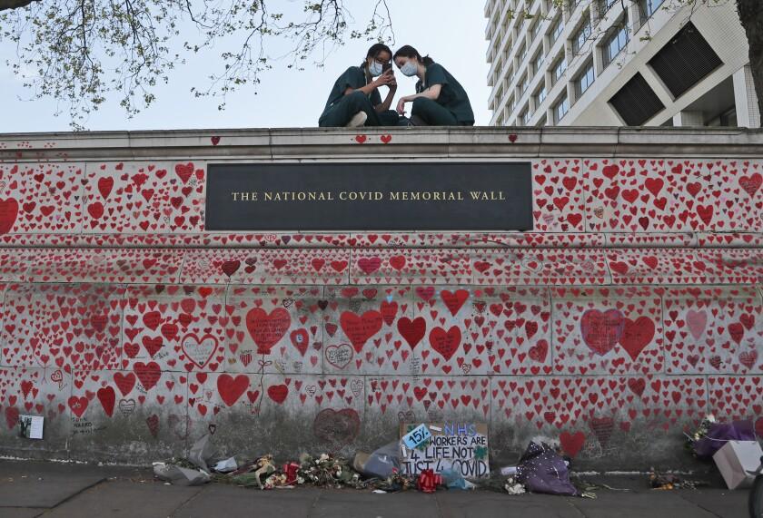 Enfermeras del Hospital St. Thomas están sentadas en el monumento nacional al COVID-19 en Londres, el 27 de abril de 2021. (AP Foto/Frank Augstein, file)