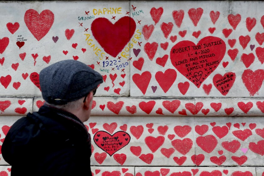 A man walks past the National Covid Memorial Wall commemorating all those who have died of coronavirus, on the Thames Embankment opposite the Houses of Parliament in London, Thursday, April 8, 2021. Bereaved families want the wall of painted hearts to remain a site of national commemoration and are asking the Prime Minister to help make the memorial permanent. (AP Photo/Frank Augstein)