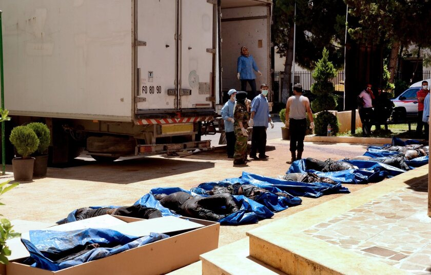 Syrian medical workers and relatives inspect bodies that are claimed to be of victims of a massacre in Khan Assal, near Aleppo, Syria.