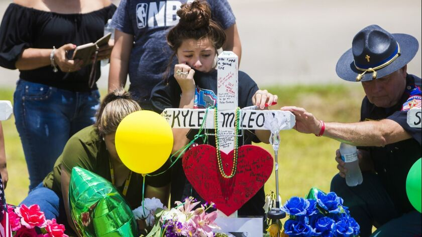 A young woman cries, Tuesday, May 22, 2018, by a memorial for Santa Fe High School freshman Aaron Ky