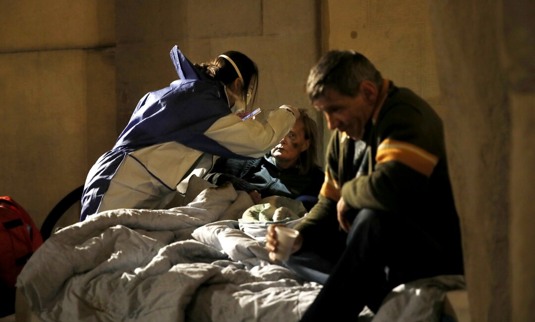 A volunteer nurse wearing a mask tends to homeless people in Milan.