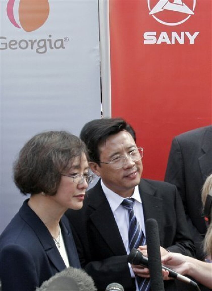 FILE - In this Sept. 12, 2007 file photo, Liang Wengen, right, chairman of Sany Heavy Industry Co., speaks to the media via an interpreter, left, during a ceremony at the state Capitol in Atlanta, Ga., announcing the Chinese manufacturer has selected Peachtree City, Ga., for its North American headquarters bringing 200 jobs to the metro Atlanta area. The Hurun Rich List 2010, China's equivalent of the Forbes list, announded Wednesday, Sept. 7, 2011, said Liang, 55, leads the country's fast-growing ranks of super-wealthy. (AP Photo/Gene Blythe, File)