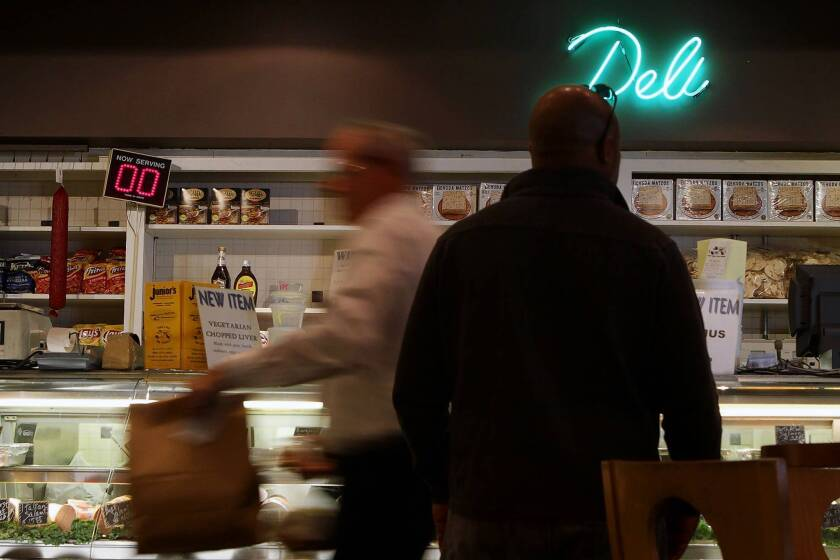 Customers order food at the deli counter during the lunch hour at Junior's Deli in Westwood. The 53-year-old restaurant will be closing at the end of the year because of a rent dispute and slump in business.