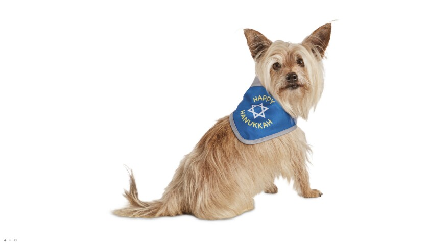 A small dog wearing a bandana with a Star of David and the words Happy Hanukkah