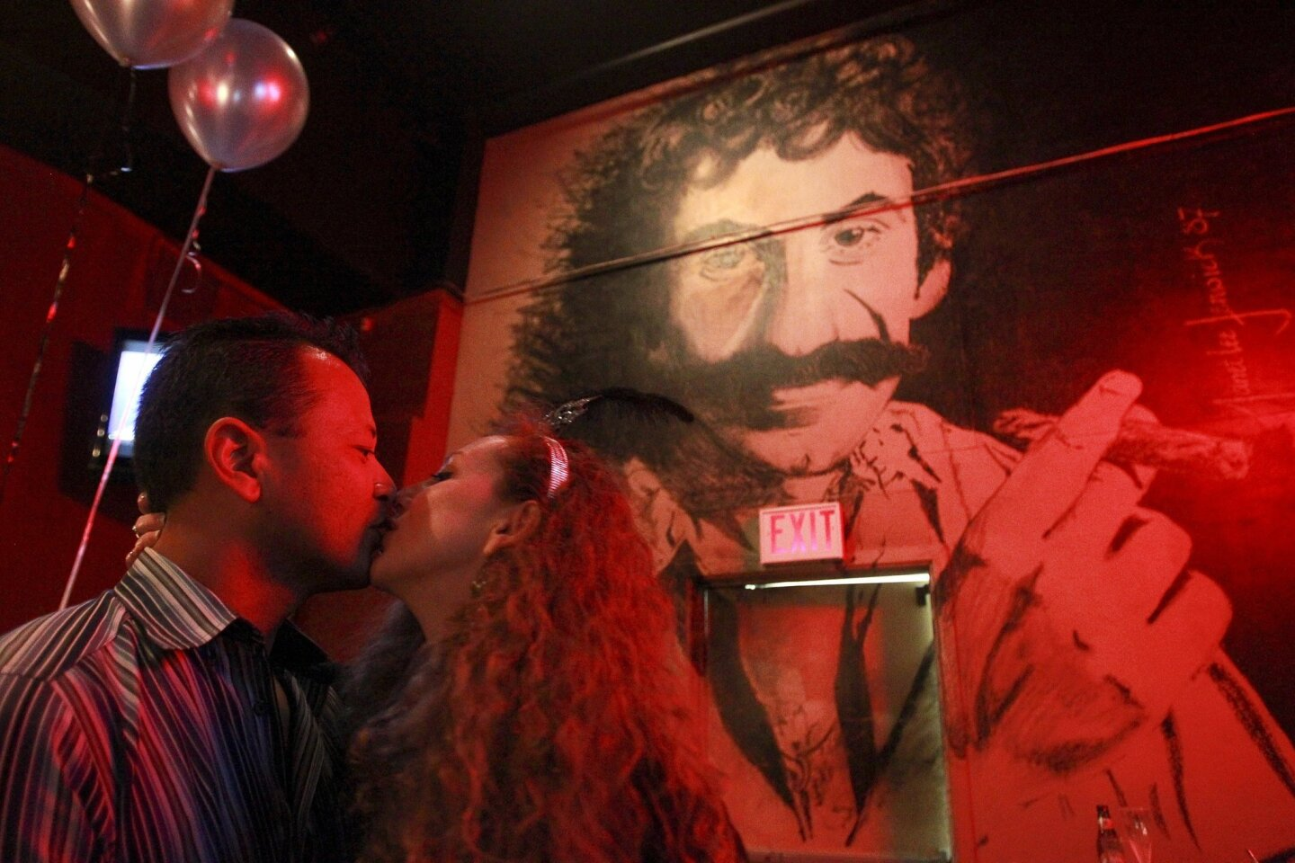 Ian Tashima and Vanessa Robbins kiss while under the large mural of singer and songwriter Jim Croce at Croce's Restaurant & Jazz Bar, which after 30 years closed its doors permanently on New Year's Day in the Gaslamp Quarter.