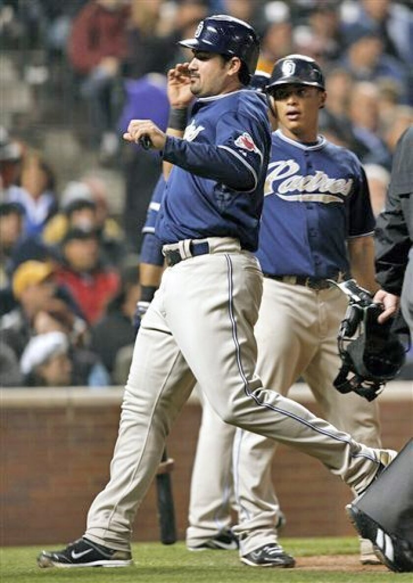 San Diego's Adrian Gonzalez scores on the tail end of teammate Will Venable's three-run double in the fifth inning of Wednesday's win over the Rockies in Denver. (AP Photo / David Zalubowski)
