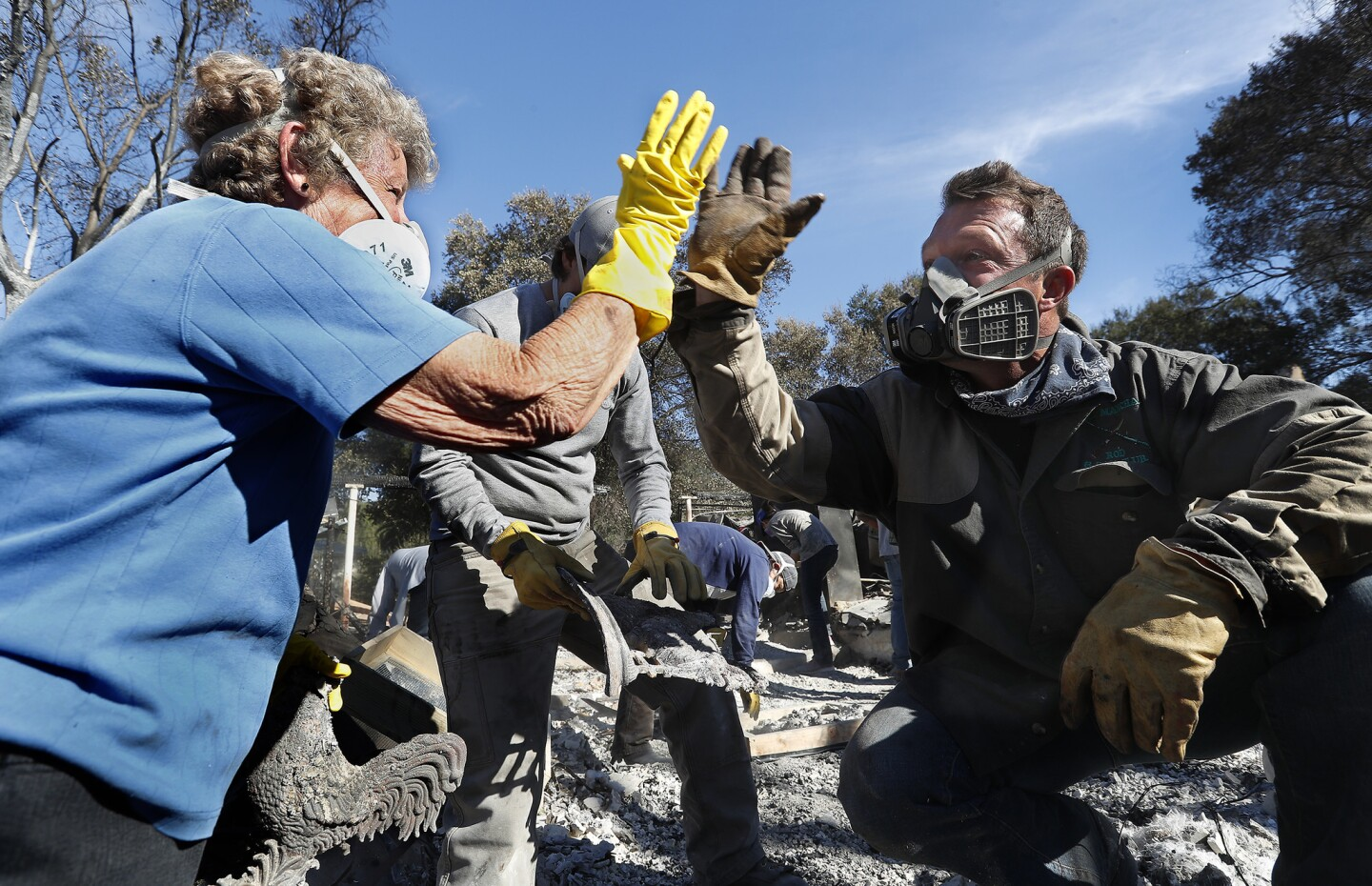 Leona Mote, left, high-fives Trevor Quirk as a team of volunteers helps sift through the rubble of her home near Ojai that burnt to the ground in the Thomas fire. Among the items recovered were her husband's wedding band, jewelry and part of a coin collection.