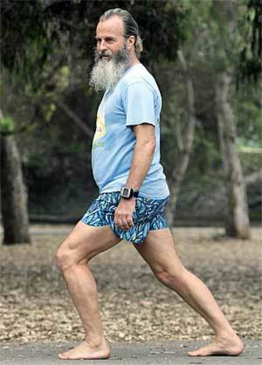 Instructor Ken Saxton demonstrates proper barefoot running posture: vertical back, bent knees and as large part as possible of the foot's surface touching the ground, after a barefoot running clinic in Huntington Beach.