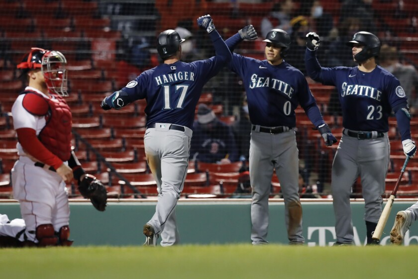 Boston Red Sox's Christian Vazquez, left, kneels at home plate as Seattle Mariners' Mitch Haniger (17) celebrates his three-run home run that also drove in Sam Haggerty (0) during the 10th inning of a baseball game, Thursday, April 22, 2021, in Boston. (AP Photo/Michael Dwyer)