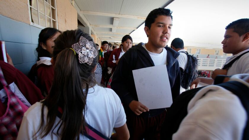 Pedro Montano Lesso, 14, center, works his way through a hallway between classes at a school in eastern Tijuana in this 2011 file photo. Educators in Baja California are grappling with the growing presence of U.S. students.