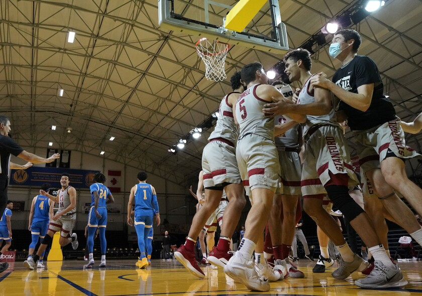 Stanford's Oscar da Silva, second from right, celebrates with teammates after his game-winning shot Jan. 23, 2021.