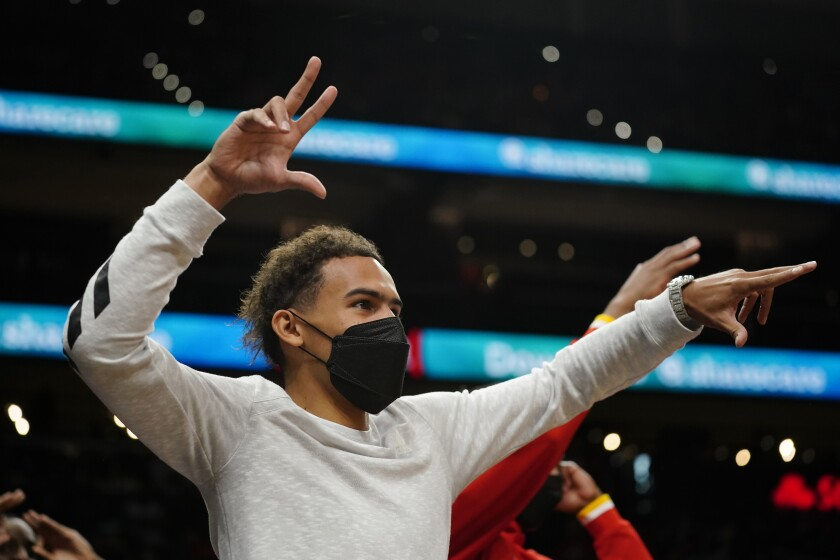 Injured Atlanta Hawks guard Trae Young reacts on the bench after an Atlanta basket against the Cleveland Cavaliers during the second half of an NBA preseason basketball game Wednesday, Oct. 6, 2021, in Atlanta. (AP Photo/John Bazemore)
