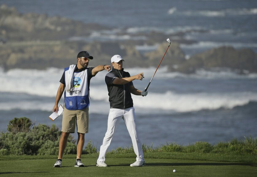 Jordan Spieth, right, stands with his caddie, Michael Greller, left, before hitting from the fourth tee of the Spyglass Hill Golf Course during the first round of the AT&T Pebble Beach National Pro-Am golf tournament Thursday, Feb. 11, 2016, in Pebble Beach, Calif. (AP Photo/Eric Risberg)