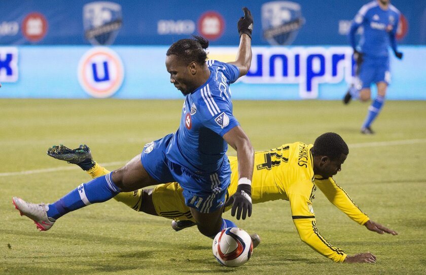 Montreal Impact's Didier Drogba, left, challenges Columbus Crew SC's Waylon Francis during second half of an MLS Eastern Conference semi-final first-leg soccer match in Montreal, Sunday, Nov. 1, 2015. (Graham Hughes/The Canadian Press via AP) MANDATORY CREDIT