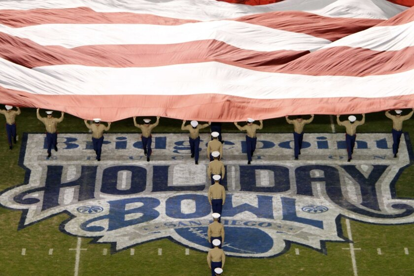 As the National Anthem is played, Marines unfurl a large American flag during the Bridgepoint Education Holiday Bowl at Qualcomm Stadium in San Diego on Thursday.