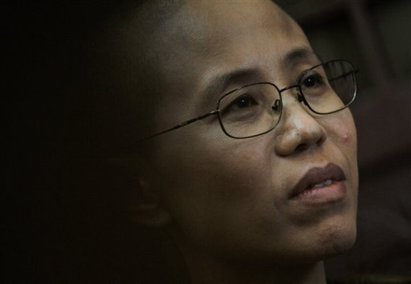 """In this Sept. 28, 2010 photo, Liu Xia, wife of Chinese dissident Liu Xiaobo speaks during an interview in Beijing, China. When the police came for Liu Xiaobo that night nearly two years ago, they didn't tell the dissident-author the reason for taking him away. The line in the detention order for """"motive"""" was blank. But everyone in Liu's dark Beijing apartment knew exactly why. Liu was hours from releasing a call for peaceful political reform in China that would represent the democracy movement's most comprehensive demand ever _ and that would earn Liu multiple nominations for this year's Nobel Peace Prize. (AP Photo/Andy Wong)"""