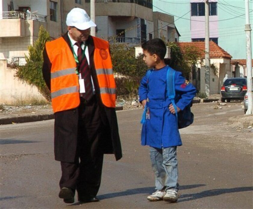 In this photo released by the Syrian official news agency SANA, an Arab League monitor speaks with a Syrian student at Al-Sabil area, in Daraa, Syria, on Tuesday Jan. 3, 2012. The Arab League called Tuesday for an emergency meeting to discuss whether to withdraw the group's monitors from Syria, where security forces are still killing protesters despite the observers' presence, an Arab official said. (AP Photo/SANA) EDITORIAL USE ONLY