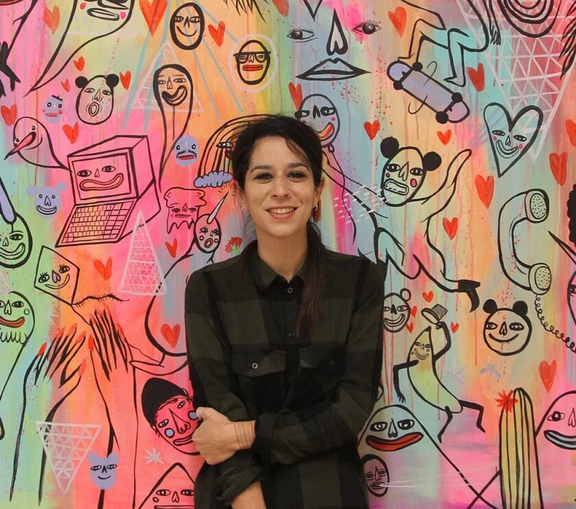 Artist Panca poses in front of her colorful mural for the New Children's Museum