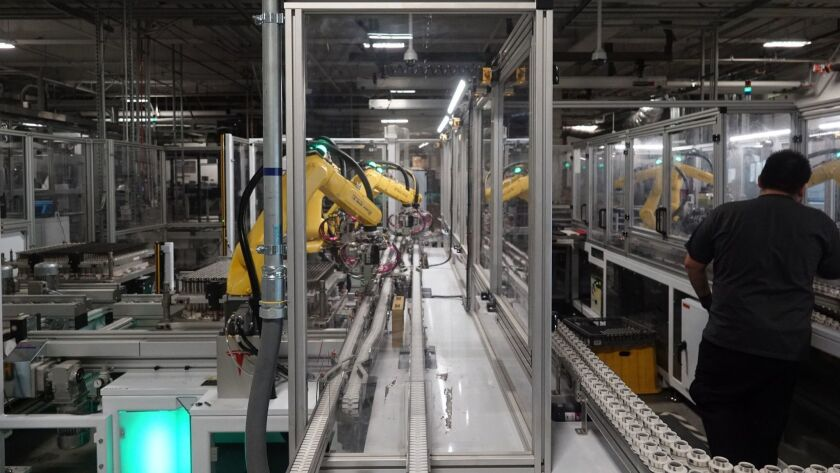 In this Dec. 3, 2018 photo, robots at the Tesla Gigafactory help assemble battery cells from Panason