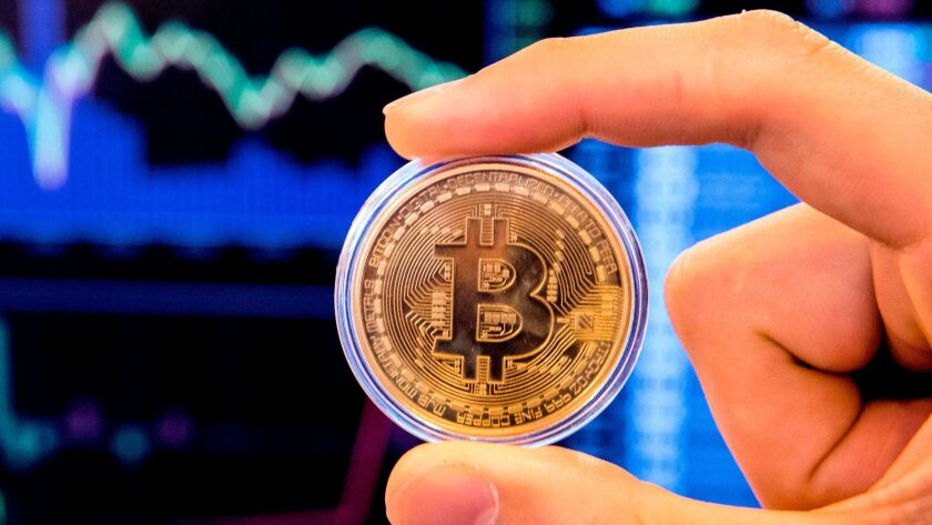 A person holds a visual representation of the digital currency bitcoin.