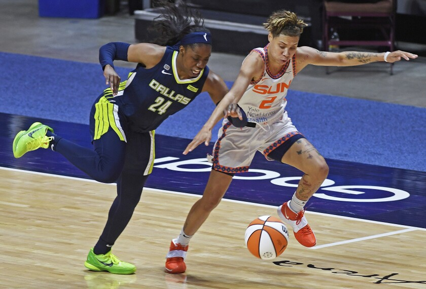 Dallas Wings guard Arike Ogunbowale deflects the ball away from Connecticut Sun guard Natisha Hiedeman during a WNBA basketball game Tuesday, June 22, 2021 at Mohegan Sun Arena in Uncasville, Conn. (Sean D. Elliot/The Day via AP)