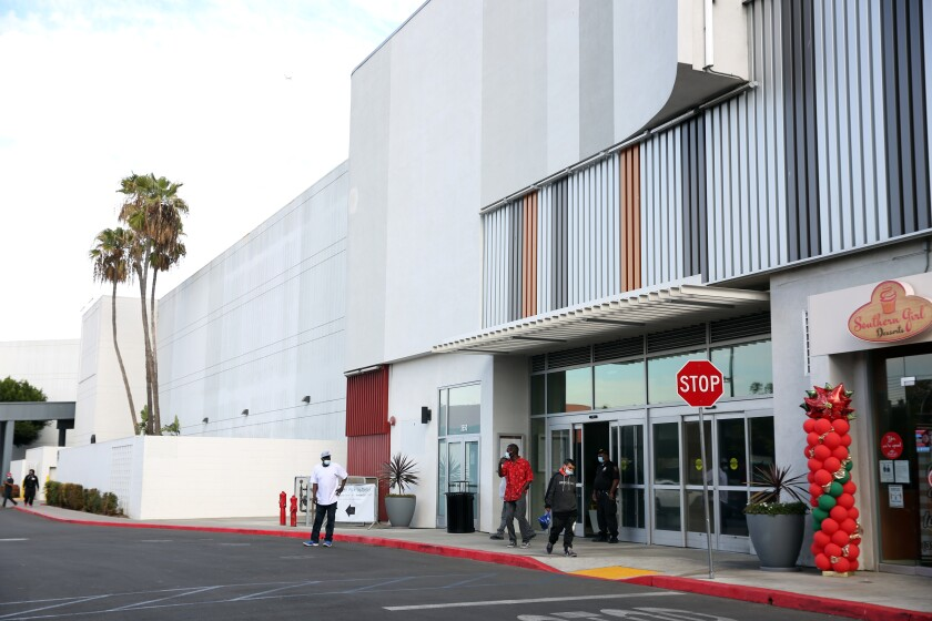 Shoppers exit the Baldwin Hills Crenshaw Mall on Dec. 8, 2020.