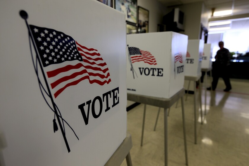 """White voting booths with the U.S. flag and the word """"vote"""" on them."""