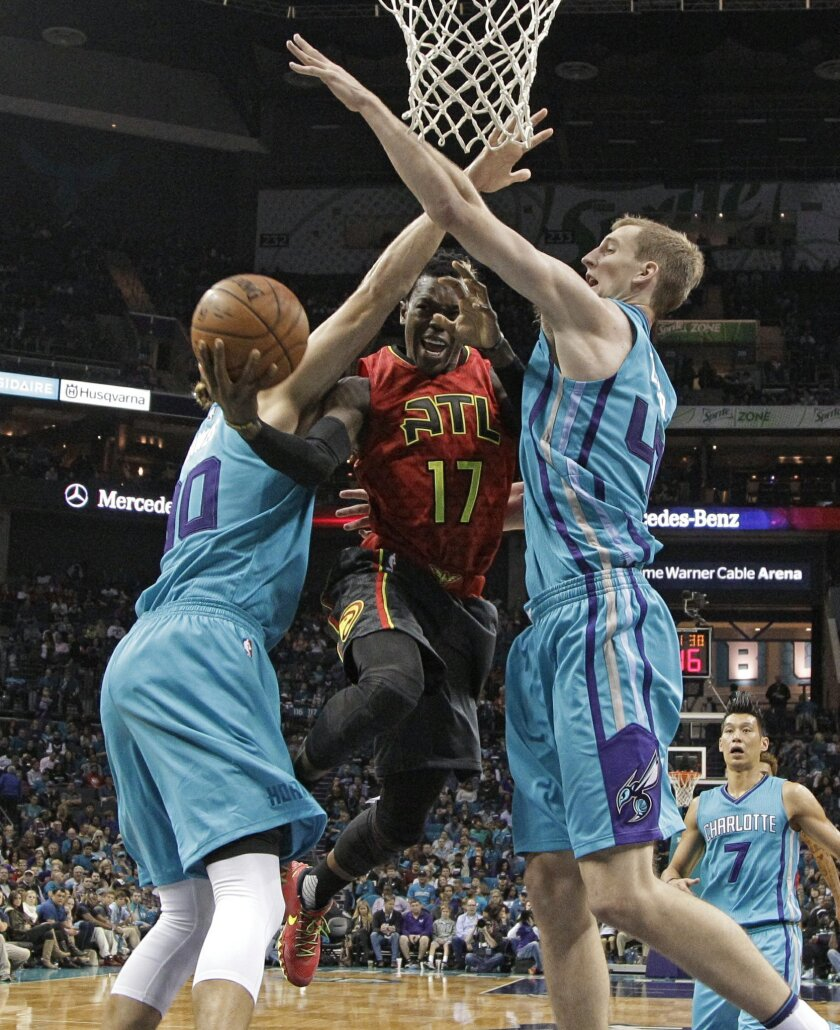 Atlanta Hawks' Dennis Schroder, center, drives between Charlotte Hornets' Cody Zeller, right, and Spencer Hawes, left, in the second half of an NBA basketball game in Charlotte, N.C., Sunday, Nov. 1, 2015. The Hawks won 94-92. (AP Photo/Chuck Burton)